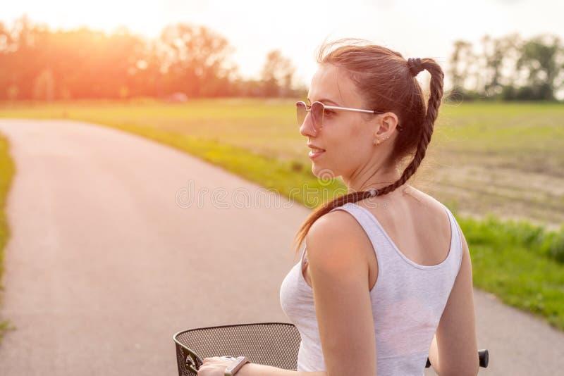 Cierre de la muchacha para arriba con la bici en la puesta del sol del verano en el camino en el parque de la ciudad El parar la  foto de archivo