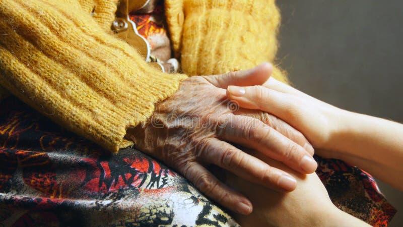 Cierre de la piel de la arruga de la mano del control de la chica joven de la mujer mayor para arriba imágenes de archivo libres de regalías
