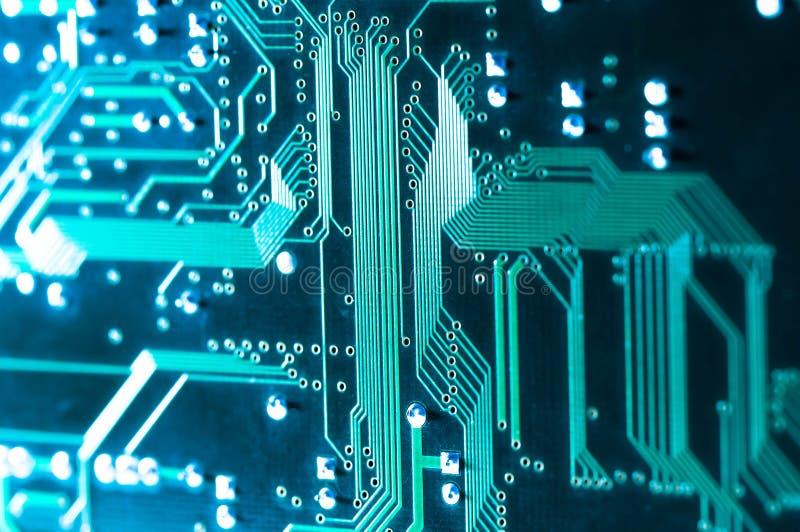 Cierre de la placa de circuito del ordenador encima del tiro macro en azul foto de archivo