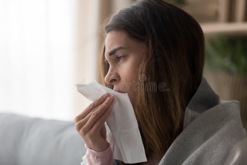 Cierre de la vista lateral encima de la mujer que sostiene el tejido del papel que estornuda imagen de archivo