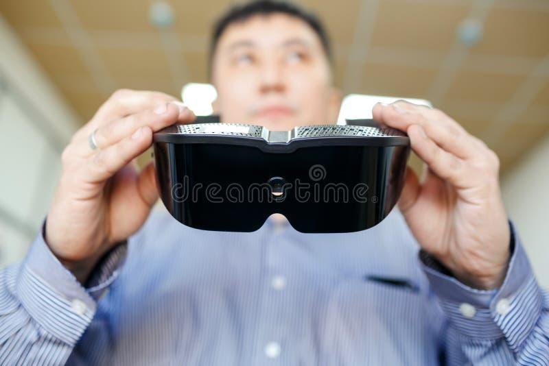 Cierre de las auriculares de la realidad virtual para arriba en manos del hombre que va a llevarlas, del concepto futuro del vr y foto de archivo libre de regalías