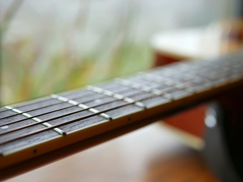 Cierre de madera acústico de la guitarra para arriba en fondo de madera con fretboard, las secuencias, y los sintonizadores para  foto de archivo libre de regalías