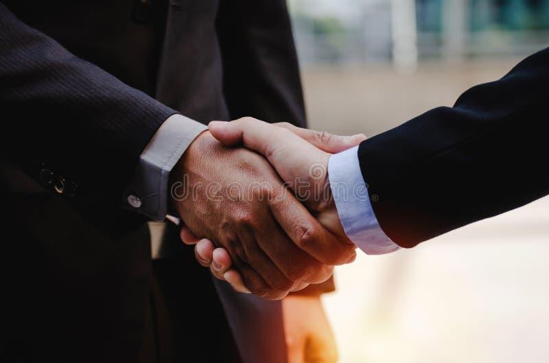 Cierre de un hombre de negocios en traje estremeciéndose las manos después de terminar una reunión de negocios en la ciudad con imagen de archivo libre de regalías