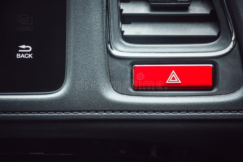 Cierre del botón de emergencia de coche de color rojo de forma rectangular en el tablero de mandos de un coche de lujo foto de archivo