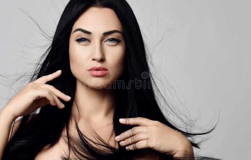 Cierre del concepto del anuncio para arriba de la morenita caliente atractiva de la mujer que cepilla delicado su pelo que agita  imagen de archivo