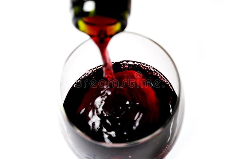 Cierre del cuello de la botella que llena el vidrio del vino rojo fotos de archivo
