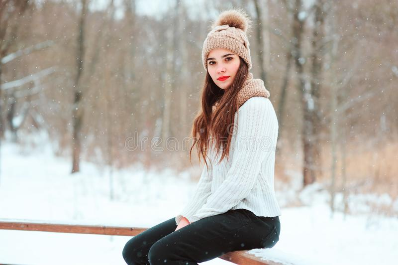 cierre del invierno encima del retrato de la mujer joven hermosa en caminar hecho punto del sombrero y del suéter al aire libre imagenes de archivo