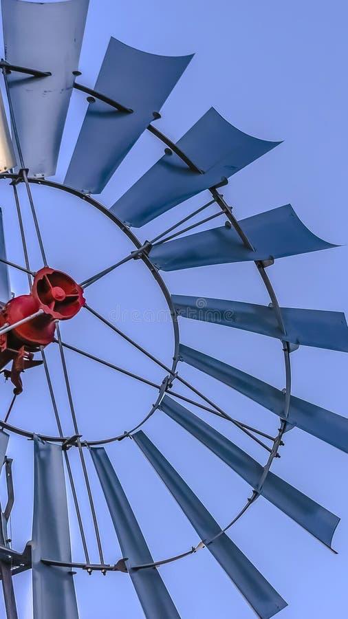 Cierre del marco del panorama para arriba de las cuchillas múltiples de un windpump con el fondo claro de cielo azul foto de archivo