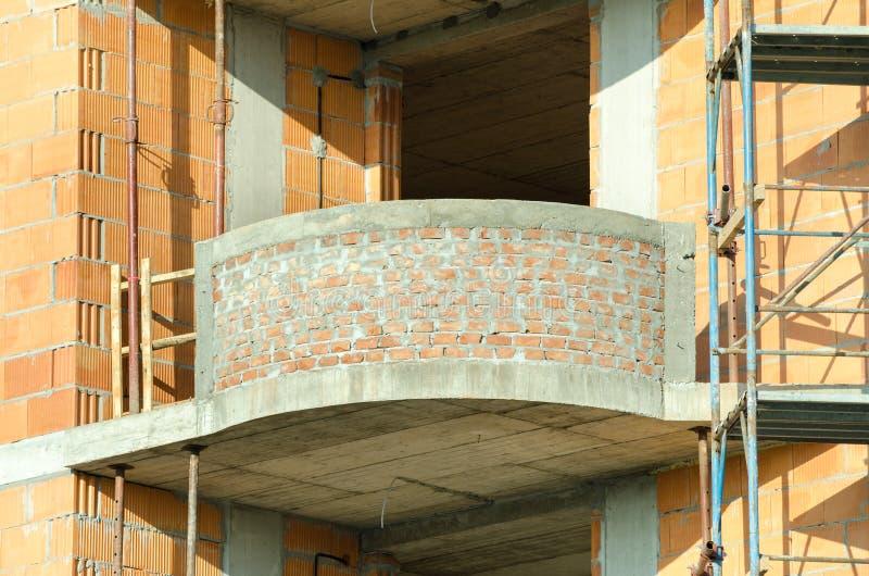 Cierre del sitio de la construcción de edificios residenciales para arriba del balcón de la terraza del ladrillo del apartamento foto de archivo libre de regalías