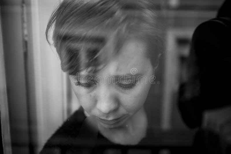 Cierre dramático encima del retrato de la mujer hermosa joven que piensa y que siente la ventana sufridora triste de la depresión fotografía de archivo libre de regalías