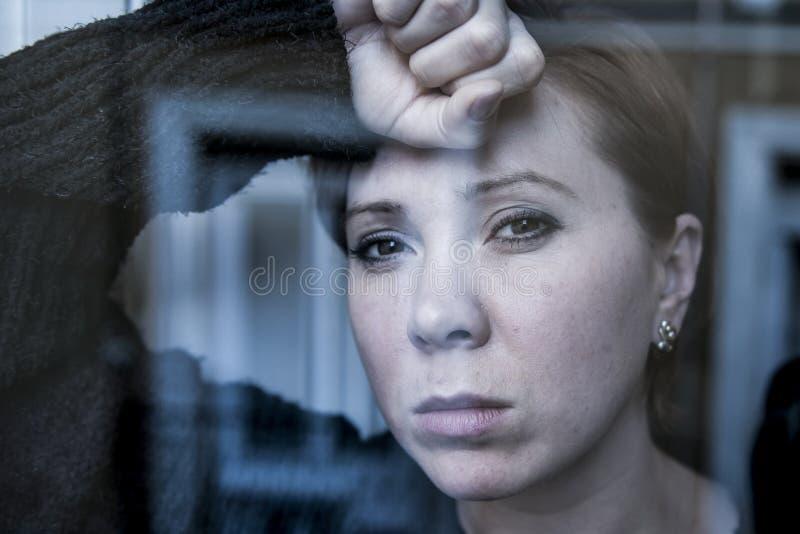 Cierre dramático encima del retrato de la mujer hermosa joven que piensa y que siente la ventana sufridora triste de la depresión imagen de archivo libre de regalías
