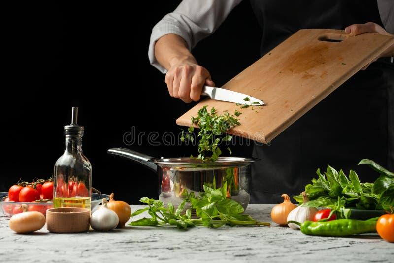 Cierre el chef& x27; manos de s, preparando una salsa de tomate italiana para el mA foto de archivo