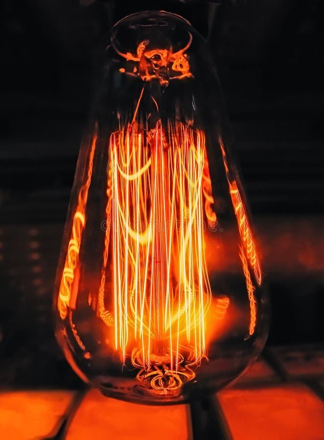 Cierre en forma de pera brillante de la lámpara de cristal clara que brilla intensamente para arriba Fondo oscuro de la lámpara r imagen de archivo