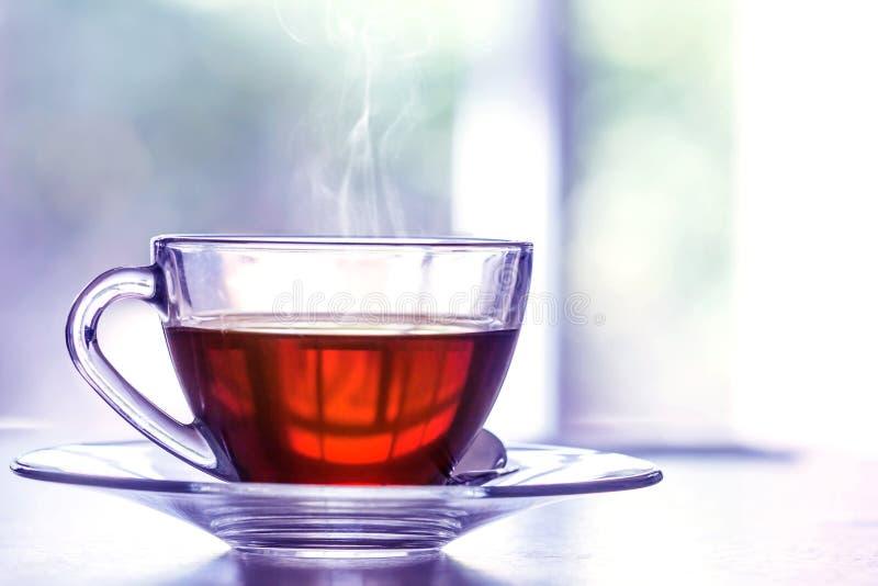 Cierre encima de caliente la taza de té negro en la tabla de madera en el ro de vida fotografía de archivo