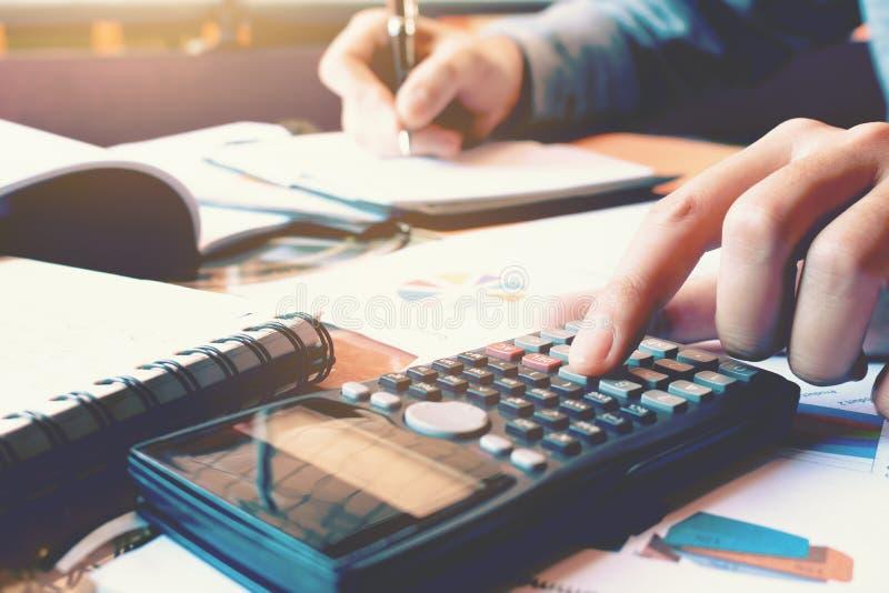 Cierre encima de la calculadora del presionado a mano de la mujer y hacer finanzas en el hom imágenes de archivo libres de regalías