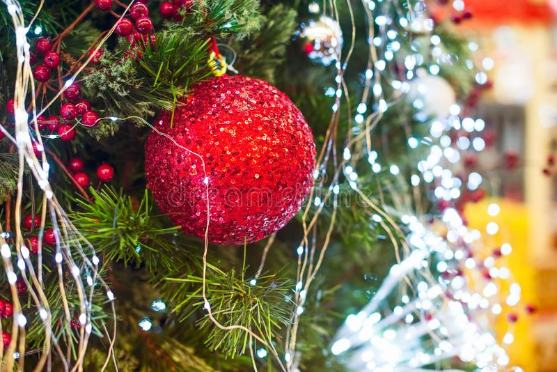 Cierre encima de la chuchería roja de las lentejuelas que cuelga en adornado con el árbol de navidad de las luces Decoraciones de fotografía de archivo libre de regalías