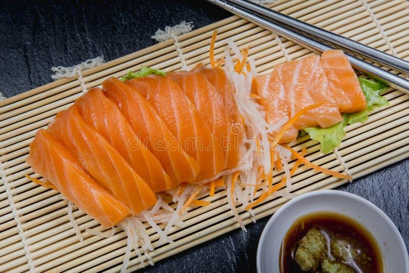 Cierre encima de la ensalada determinada del sashimi de color salmón fresco en la placa de bambú, comida japonesa imagenes de archivo