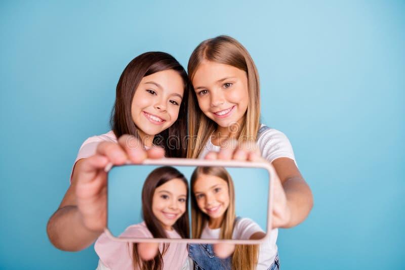 Cierre encima de la foto dos poco ella su teléfono bonito largo del pelo de las muchachas morenas rubias hacer que toman los self imágenes de archivo libres de regalías