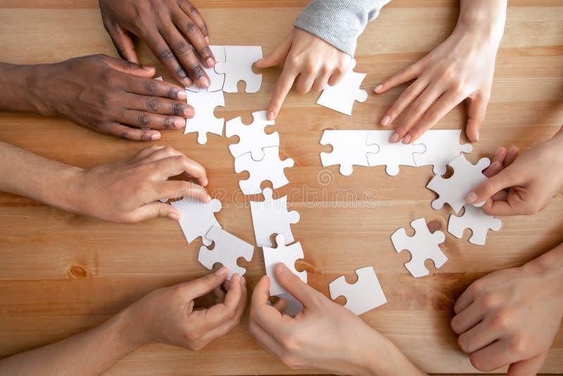 Cierre encima de la gente multirracial, rompecabezas de junta del equipo, trabajo en equipo del éxito imagen de archivo