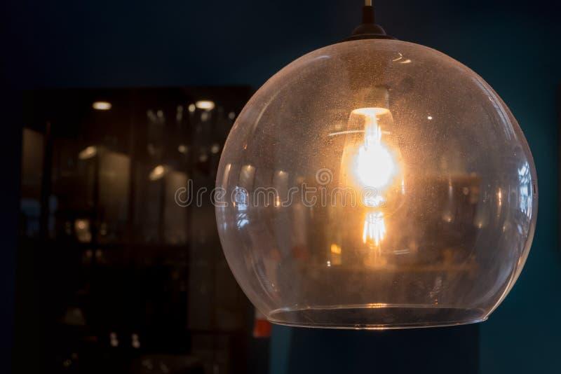 Cierre encima de la lámpara moderna que brilla intensamente en la oscuridad fotografía de archivo
