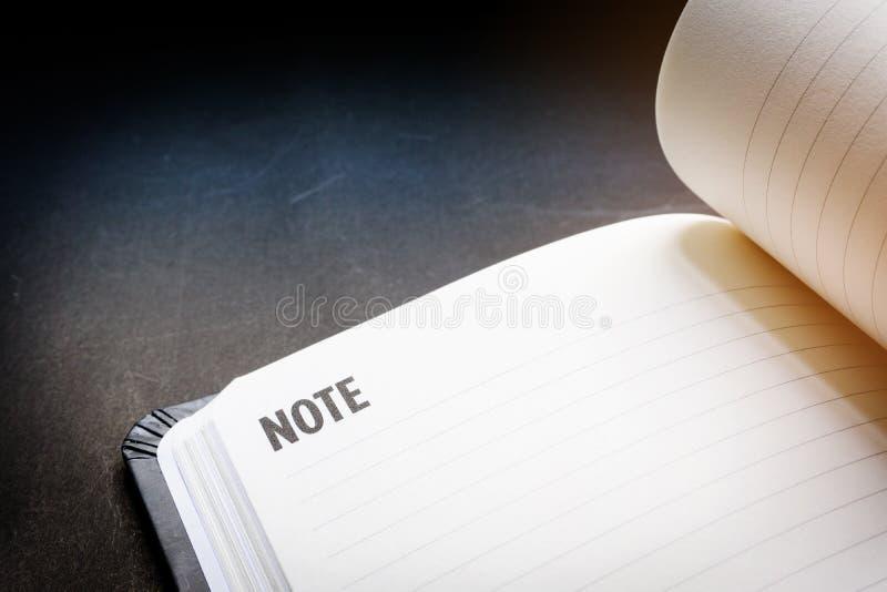 Cierre encima de la l?nea en blanco abierta cuaderno en fondo negro del escritorio en tono de iluminaci?n dram?tico Concepto para imagen de archivo