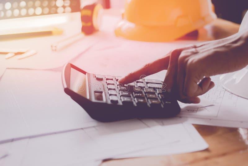 Cierre encima de la mano del hombre usando bonusOr calculador de la calculadora la otra remuneración a los empleados para aumenta fotografía de archivo libre de regalías