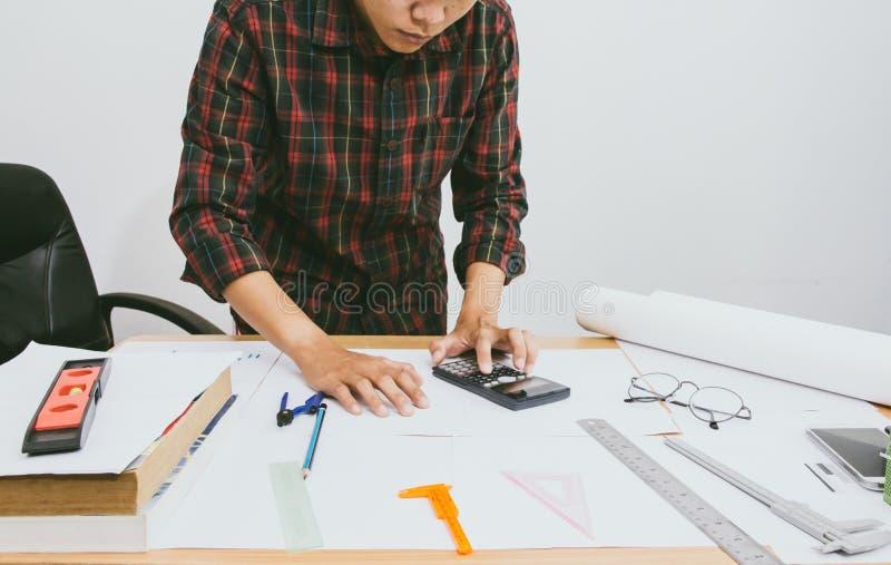 Cierre encima de la mano del hombre usando bonusOr calculador de la calculadora la otra remuneraci?n a los empleados para aumenta imagen de archivo libre de regalías