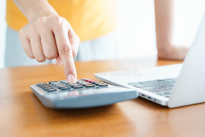 cierre encima de la mano de la imagen usando la calculadora para el negocio de la contabilidad en el fondo del escritorio tenga o imagenes de archivo