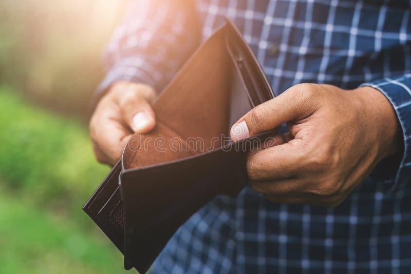 Cierre encima de la mano masculina que sostiene la cartera vacía ningún dinero en las manos fotos de archivo