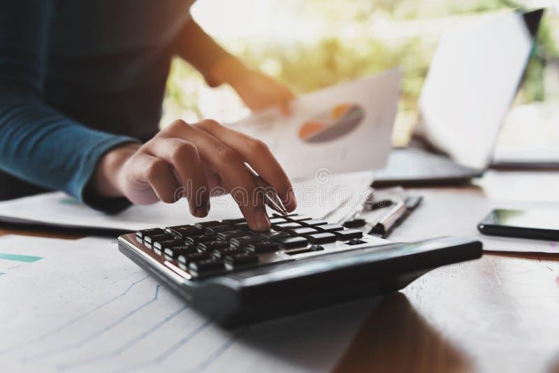 cierre encima de la mano de la mujer de negocios usando la calculadora para trabajar imágenes de archivo libres de regalías