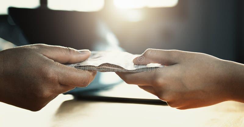 cierre encima de la mano que da el dinero para el socio fotografía de archivo libre de regalías