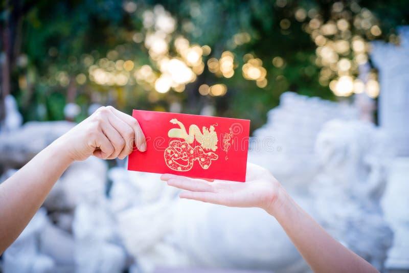 Cierre encima de la mano que lleva a cabo la letra roja, enviando y recibiendo símbolos rojos del sobre del Año Nuevo chino en fo foto de archivo libre de regalías