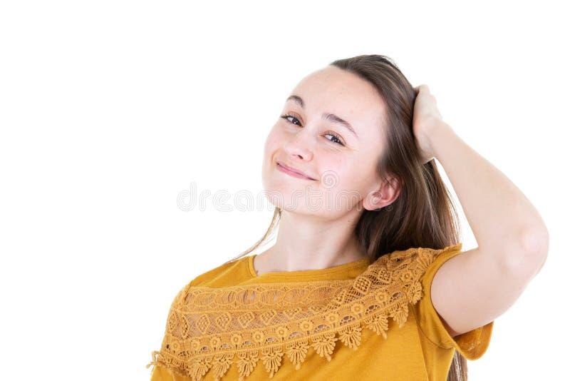Cierre encima de la mujer atractiva hermosa joven del retrato que juega con su pelo en el espacio blanco del fondo y de la copia imagen de archivo