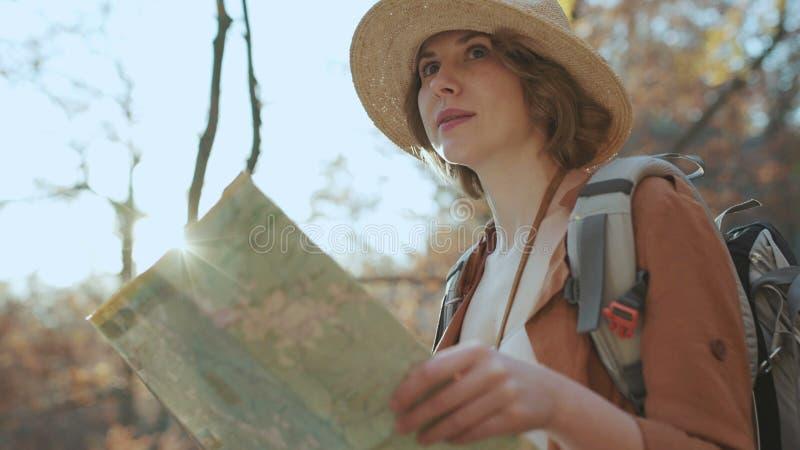 Cierre encima de la mujer joven atractiva en sombrero elegante y de un mapa turístico en sus manos que miran alrededor foto de archivo libre de regalías