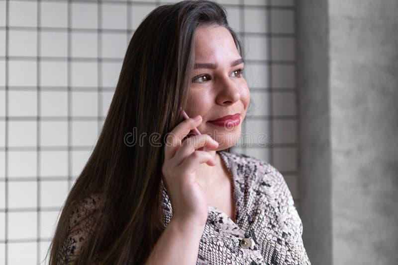 Cierre encima de la mujer joven de la oficina que habla con alguien en su teléfono fotos de archivo libres de regalías