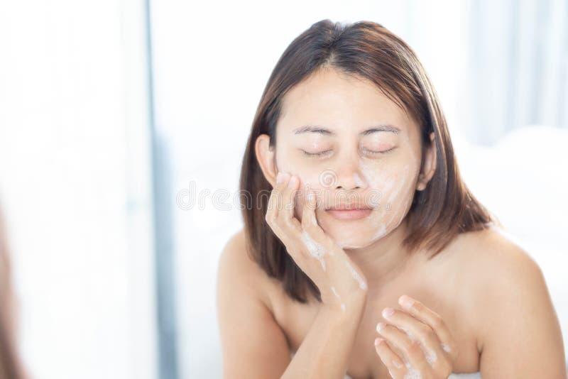 Cierre encima de la mujer que mira la reflexión en el espejo para la cara que se lava con espuma en el concepto del cuarto de bañ fotografía de archivo libre de regalías