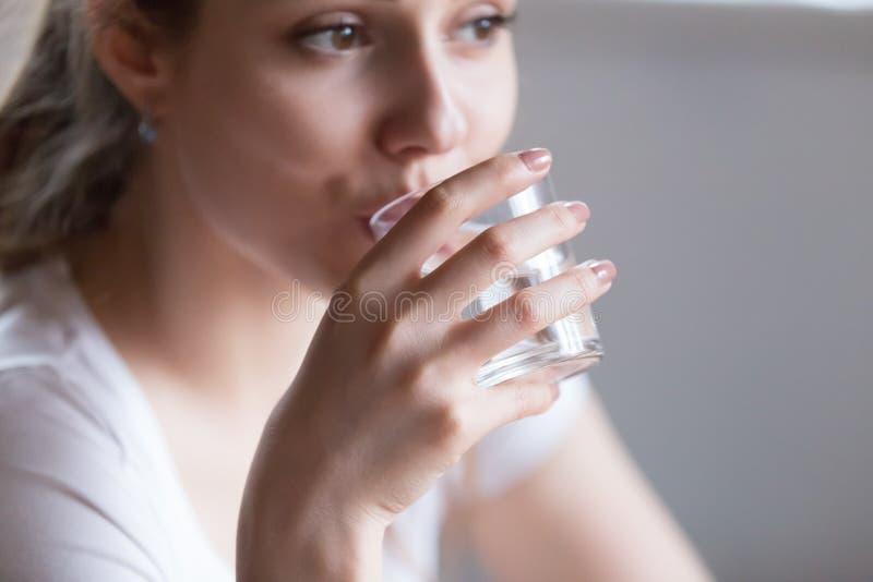 Cierre encima de la mujer que sostiene el agua de cristal de la bebida imagen de archivo