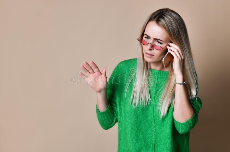Cierre encima de la mujer rubia joven que habla con alguien en su teléfono móvil mientras que mira en la distancia con la expresi foto de archivo