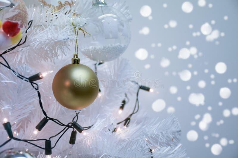 Cierre encima de la Navidad blanca y bola de oro en ramas del abeto con el fondo del bokeh imagen de archivo libre de regalías