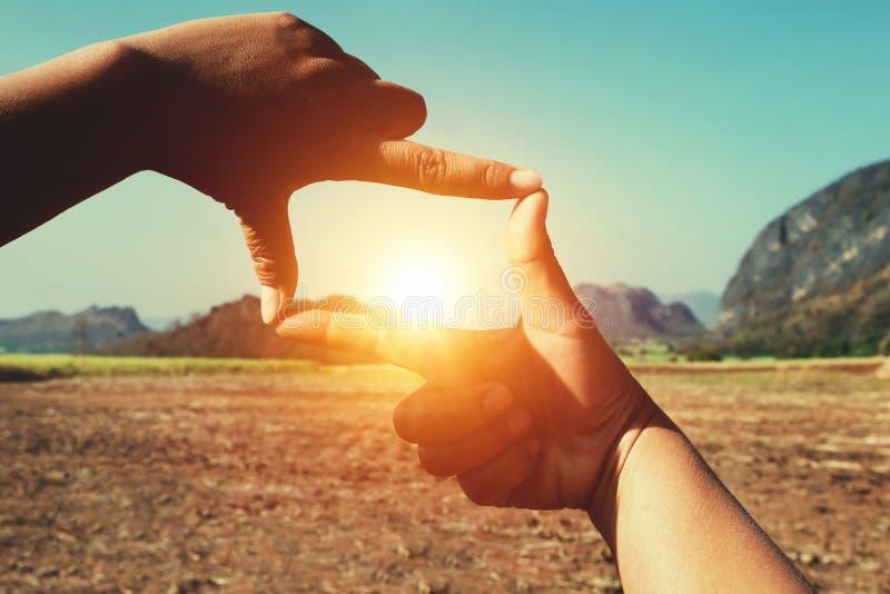 cierre encima de la opinión que enmarca de la mano distante fotografía de archivo