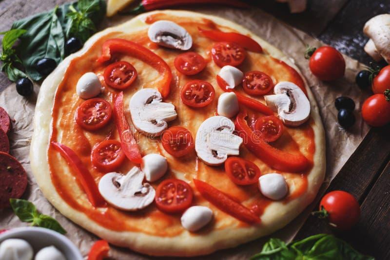 Cierre encima de la pizza hecha en casa italiana cruda con los ingredientes imagen de archivo libre de regalías