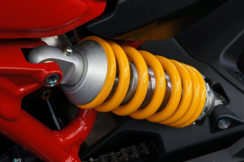 Cierre encima de la primavera amarilla y de la motocicleta posterior de los amortiguadores de choque fotos de archivo