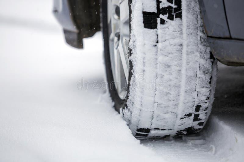 Cierre encima de la rueda de coche del detalle con el nuevo protector negro del neum?tico de goma en el camino nevado del inviern fotografía de archivo libre de regalías