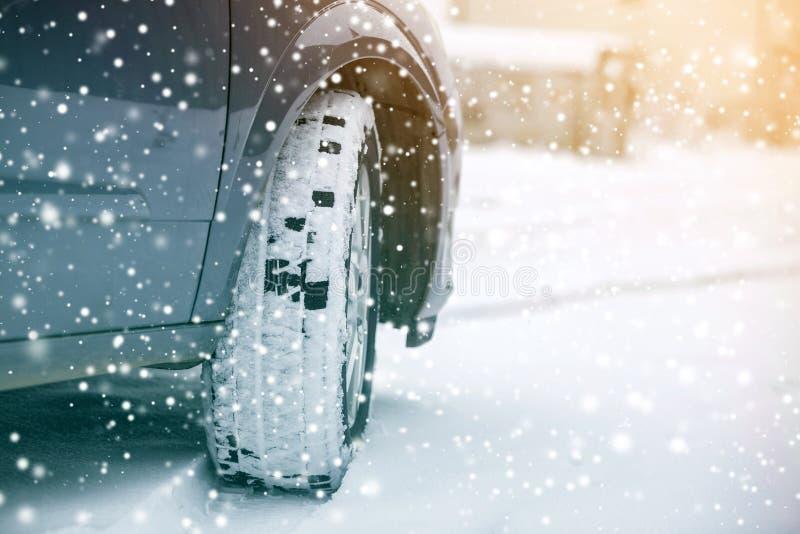 Cierre encima de la rueda de coche del detalle con el nuevo protector negro del neum?tico de goma en el camino nevado del inviern foto de archivo libre de regalías