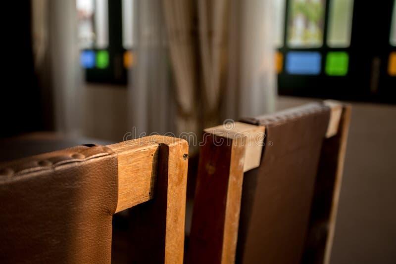 Cierre encima de la silla de madera del viejo estilo en la parte posterior con la sombra de la luz del sol imagen de archivo