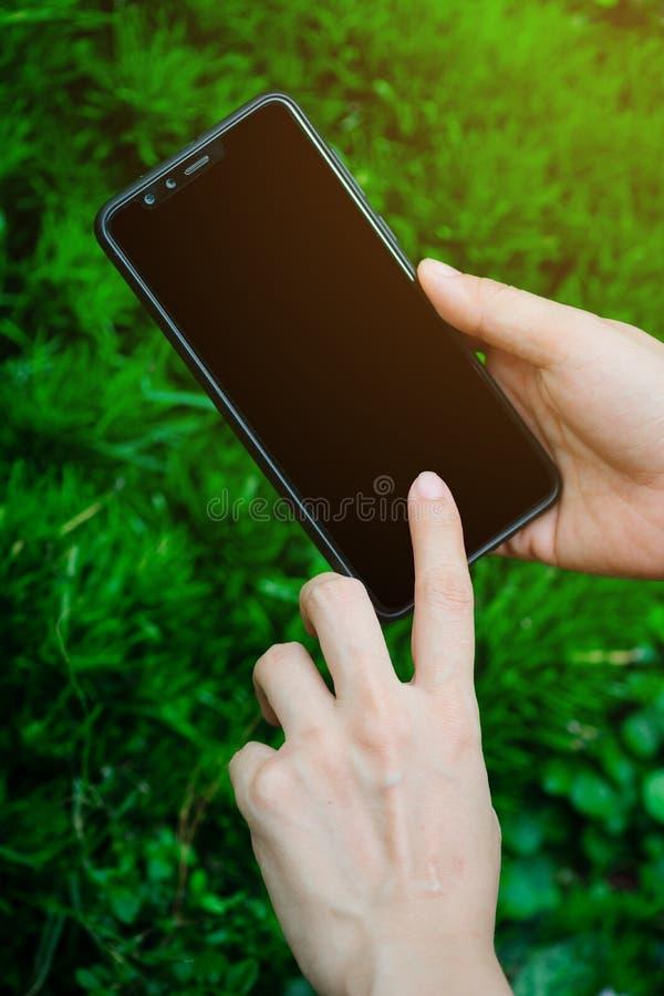 Cierre encima de la tenencia de la mano de la mujer joven y de la pantalla táctil en el smartphone negro moderno falso para arrib foto de archivo