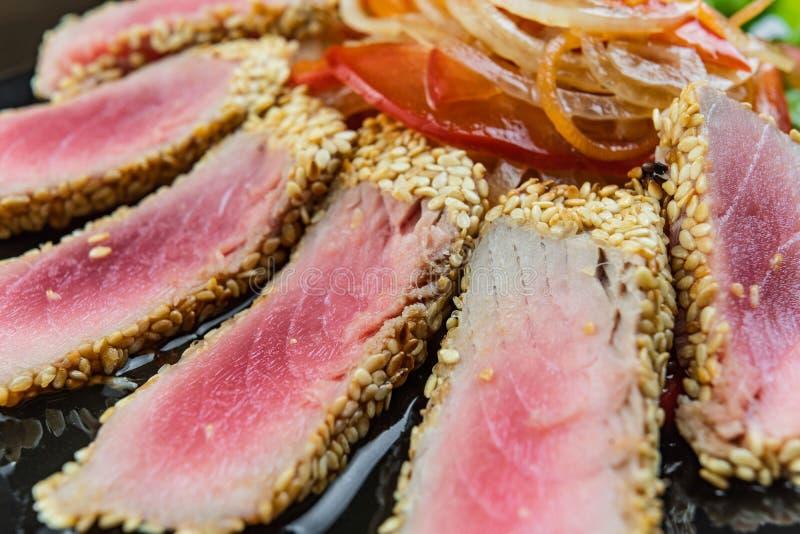 Cierre encima de la vida inmóvil de Tuna Steaks Crusted asada con las hierbas y las semillas de sésamo en Gray Surface oscuro fotos de archivo
