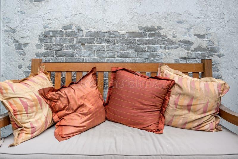 Cierre encima de las almohadas coloridas en el sofá de madera imagenes de archivo