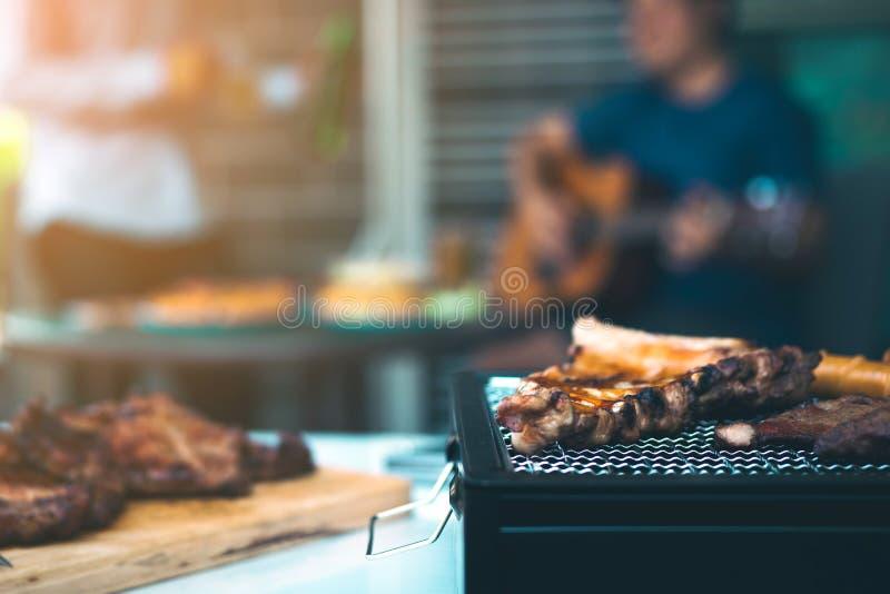 Cierre encima de las carnes asadas a la parrilla y de la diversa comida en la parrilla y celebraciones de los amigos que est?n to fotos de archivo