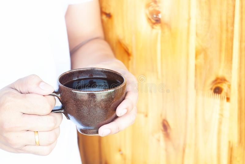 Cierre encima de las manos del hombre que sostienen la taza de caf? Concepto de la forma de vida imagen de archivo